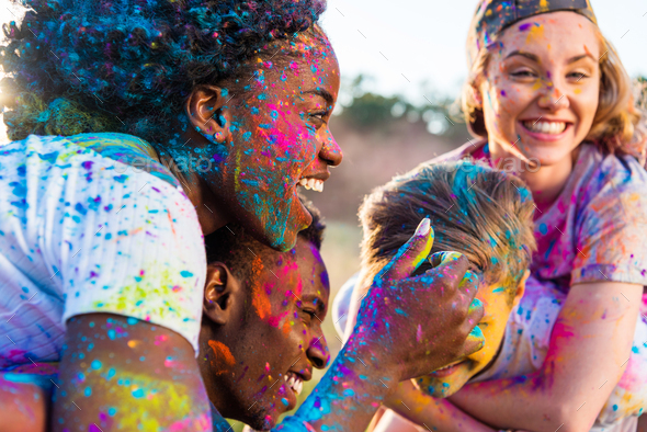 Happy Young Multiethnic Couples With Colorful Paint on Clothes Piggybacking at Holi Festival - Stock Photo - Images