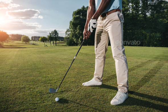 Cropped Shot of Golfer Holding Club and Hitting Ball on Green Grass - Stock Photo - Images