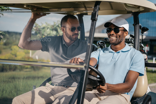 Portrait of Smiling Man Riding Golf Cart With Friend Sitting Near By - Stock Photo - Images