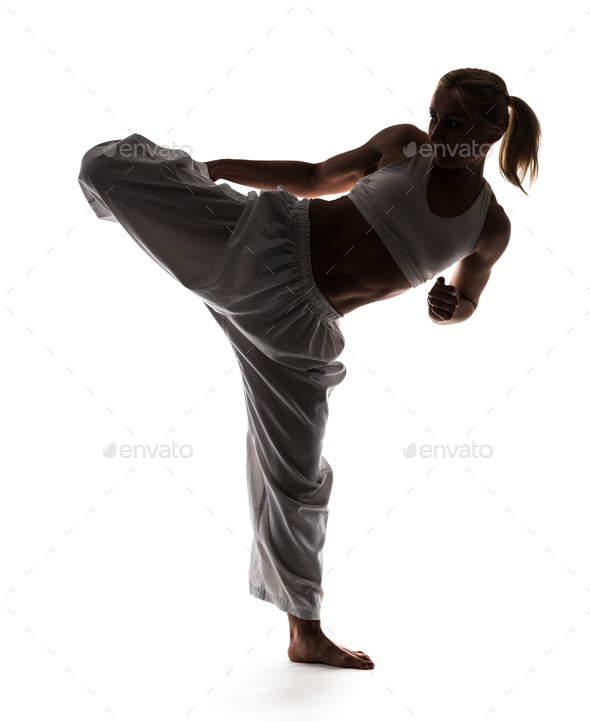 Karate woman posing standing on one leg - Stock Photo - Images