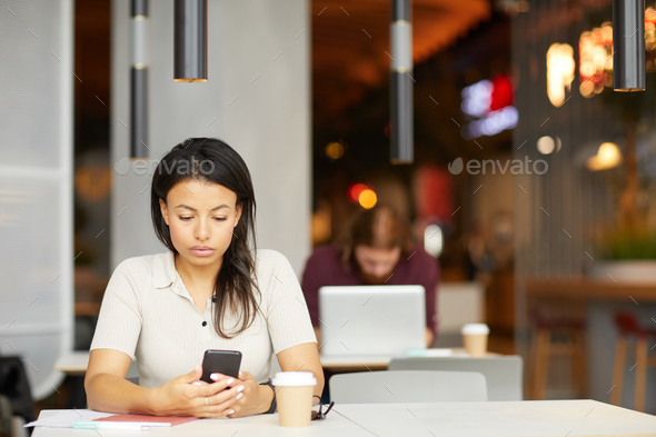 Woman with phone in cafe - Stock Photo - Images