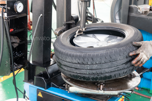 Series of worker removing tire from rim with removal machinery - Stock Photo - Images