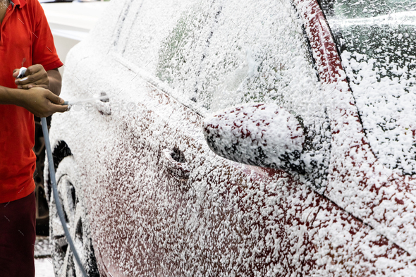 Detergent soap foam sprayed onto car at garage before washing - Stock Photo - Images
