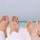 Male's and woman's legs on the white sand near the sea. - PhotoDune Item for Sale