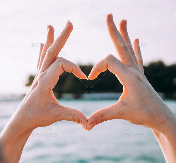 Woman making a heart shape with her hands and fingers - Stock Photo - Images