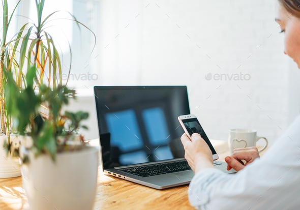 Smiling brunette woman using mobile phone with opened laptop at home - Stock Photo - Images