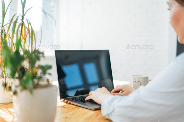 woman freelancer in casual clothes with laptop and cup of tea work at home - Stock Photo - Images