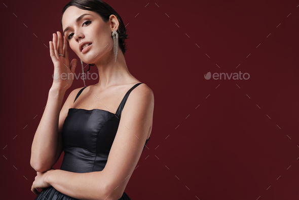 Image of charming young fashion woman wearing dress looking at camera - Stock Photo - Images