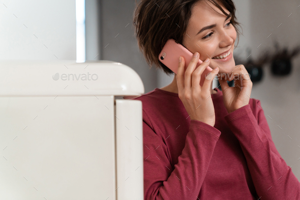 Photo of joyful young woman smiling and using smartphone - Stock Photo - Images