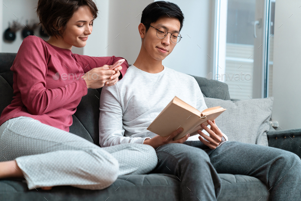Photo of pleased multinational couple reading book and using smartphone - Stock Photo - Images