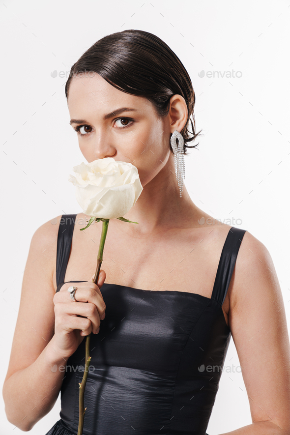 Image of charming young pretty woman holding flower and looking at camera - Stock Photo - Images