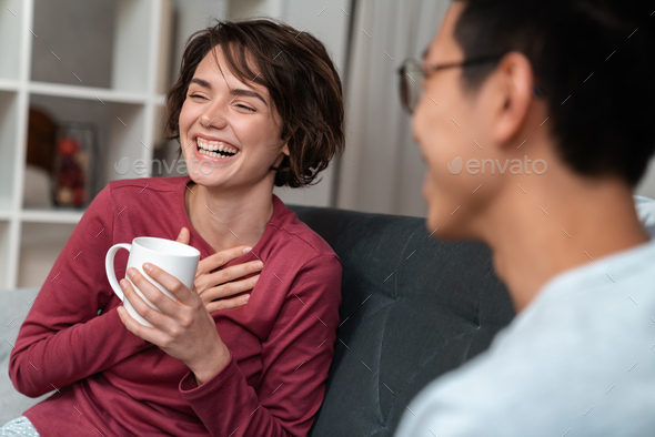 Photo of cheerful multinational couple talking and drinking tea - Stock Photo - Images