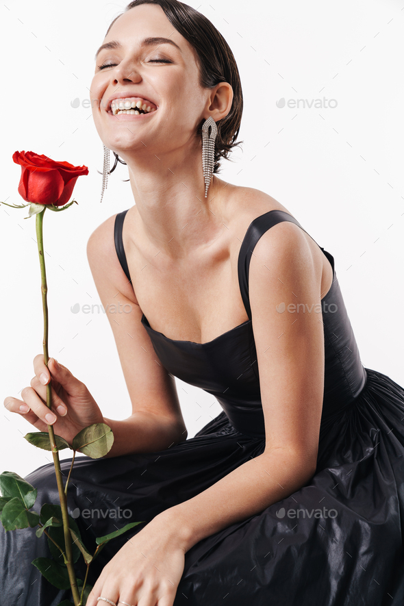 Image of charming young pretty woman smiling and holding flower - Stock Photo - Images