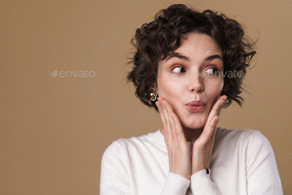 Image of excited beautiful woman expressing surprise at camera - Stock Photo - Images
