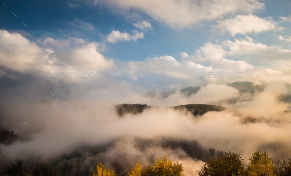 Foggy mountains under sky with clouds - Stock Photo - Images