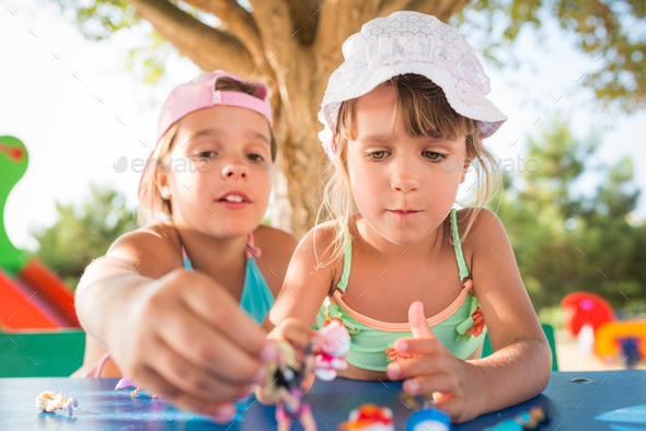Two little cute girls playing dolls outdoors - Stock Photo - Images