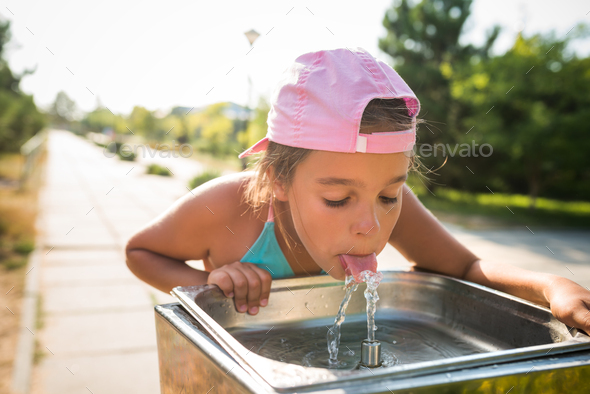 Cute thirsty girl drinks water from drinking sink - Stock Photo - Images