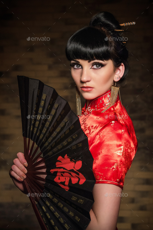 girl in a red Japanese silk dress qipao in a dark room - Stock Photo - Images