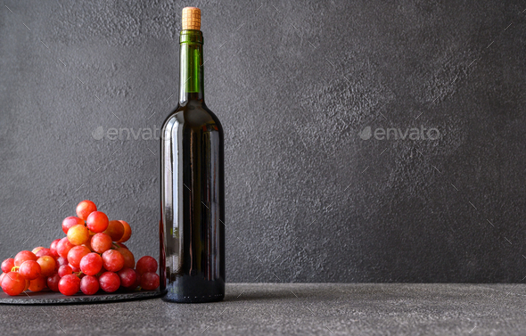 Bottle of wine with bunch of grapes - Stock Photo - Images