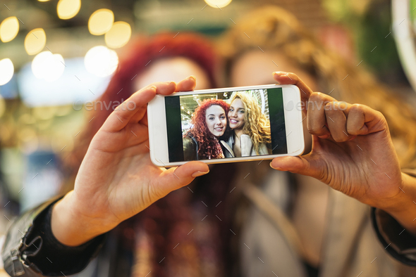 Young friends taking a selfie with cellphone. - Stock Photo - Images