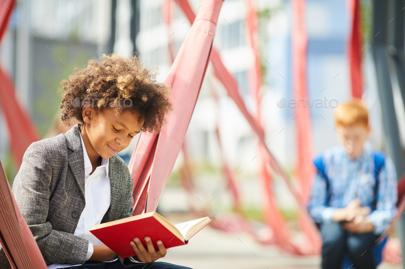 Little boy reading outdoors - Stock Photo - Images