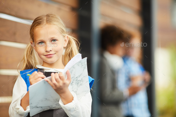 Little girl making notes in textbook - Stock Photo - Images