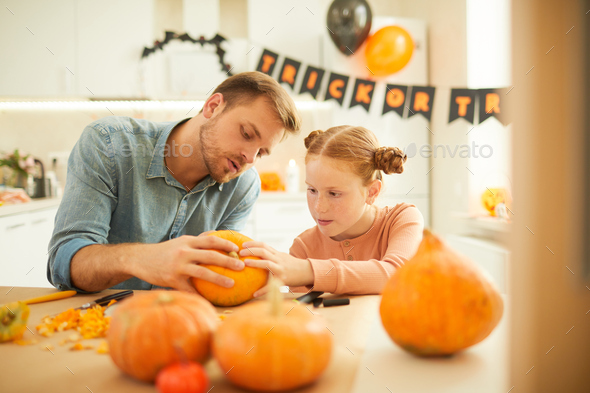 Family with pumpkins sitting at home - Stock Photo - Images