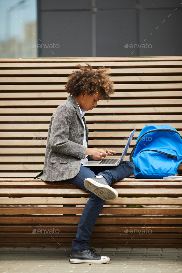 Schoolboy typing on laptop outdoors - Stock Photo - Images
