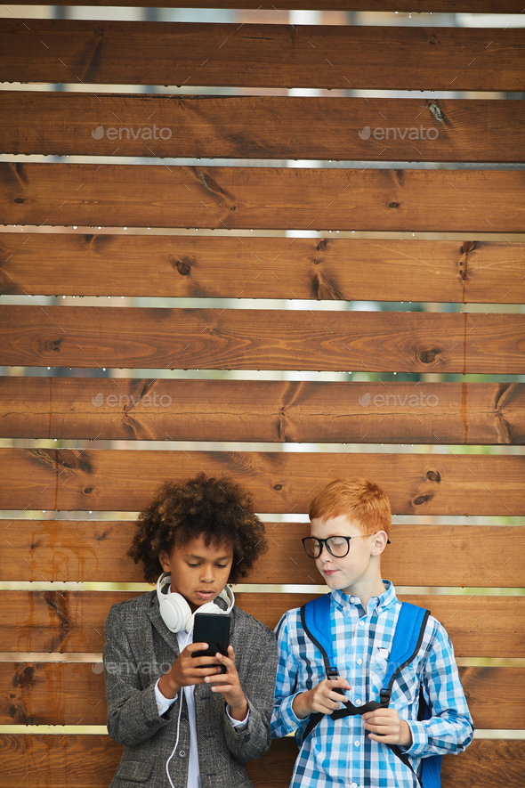 Schoolboys using mobile phone - Stock Photo - Images