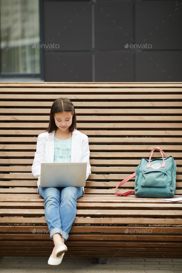 Schoolgirl using laptop outdoors - Stock Photo - Images