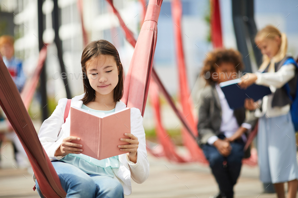 Schoolgirl with book outdoors - Stock Photo - Images