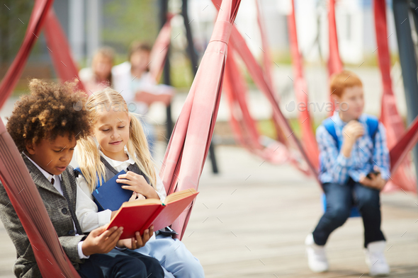 School children reading books outdoors - Stock Photo - Images