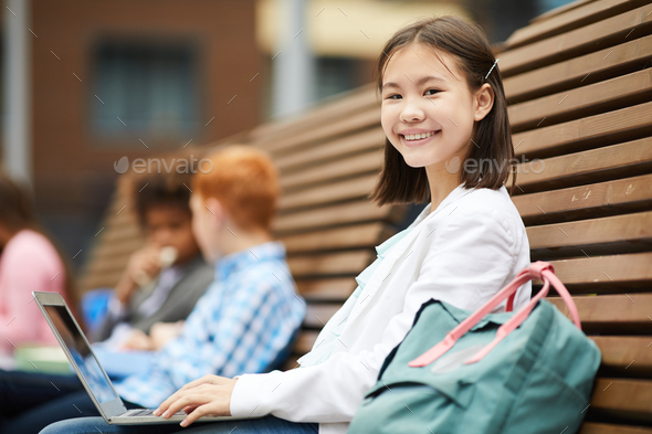 Schoolgirl with laptop outdoors - Stock Photo - Images