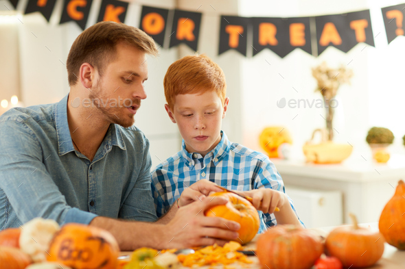 Boy carving pumpkin with father - Stock Photo - Images