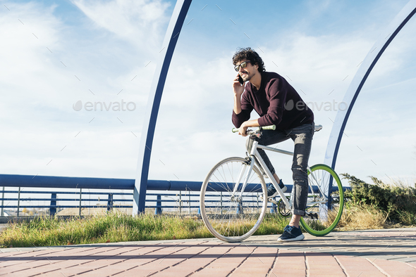 Handsome young man with mobile phone and fixed gear bicycle. - Stock Photo - Images