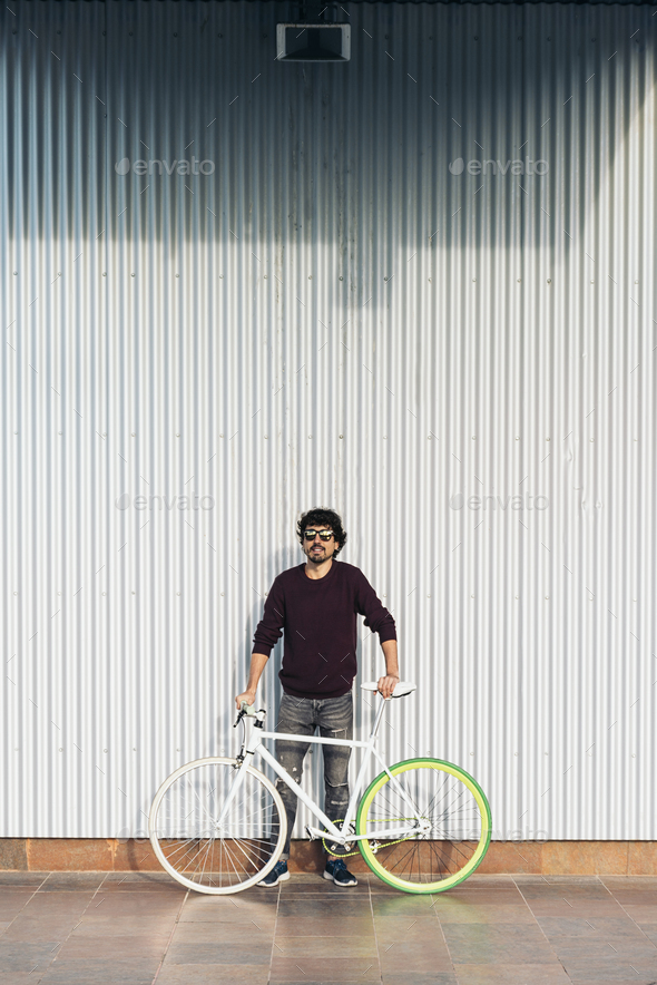 Handsome young man with fixed gear bicycle in the street - Stock Photo - Images