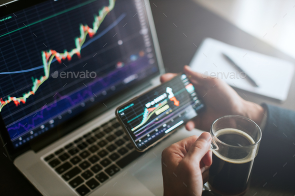 investment stockbroker predicting bitcoin price trend movement using laptop and phone - Stock Photo - Images