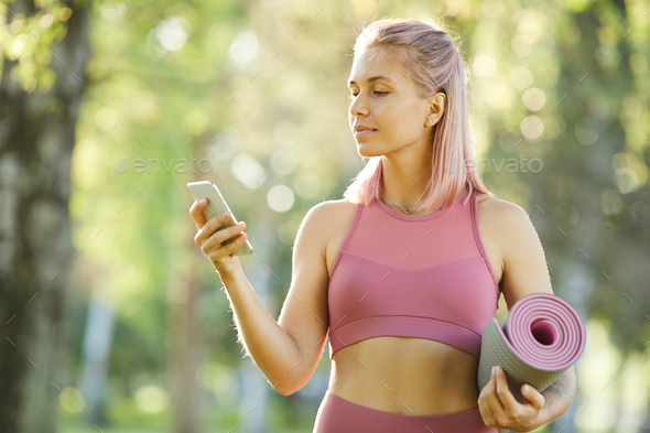 Sporty woman using phone - Stock Photo - Images