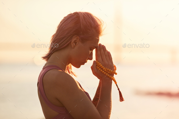 Woman practicing yoga during sunset - Stock Photo - Images