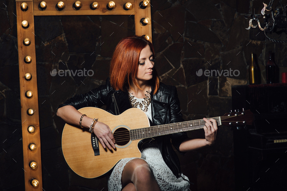 young girl with red hair with an acoustic guitar - Stock Photo - Images