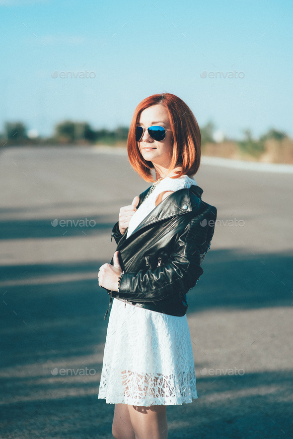 red-haired girl in a black jacket and blue glasses - Stock Photo - Images