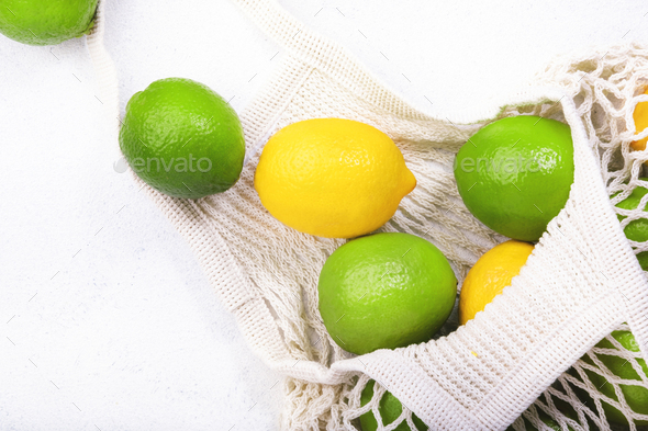 Organic lemons and limes in reusable eco-friendly string mesh bag - Stock Photo - Images