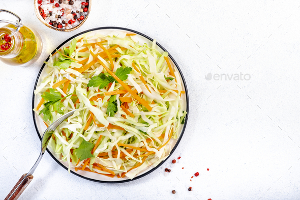 White cabbage salad coleslaw with carrot on white kitchen table - Stock Photo - Images