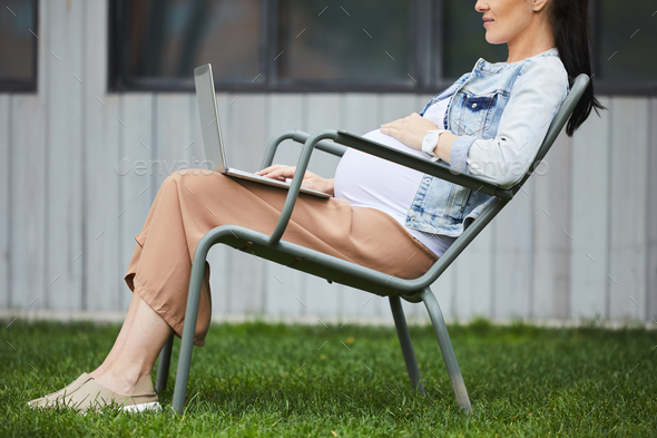 Pregnant woman working online on laptop - Stock Photo - Images