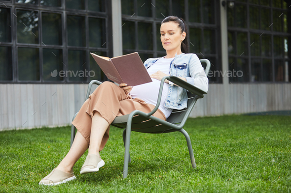 Pregnant woman with book enjoying the summer - Stock Photo - Images