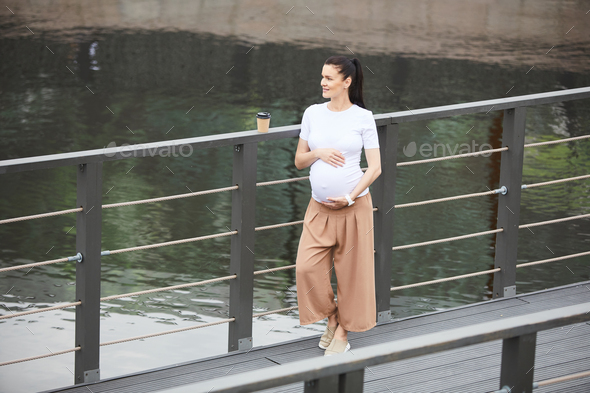 Pregnant woman dreaming on the bridge - Stock Photo - Images