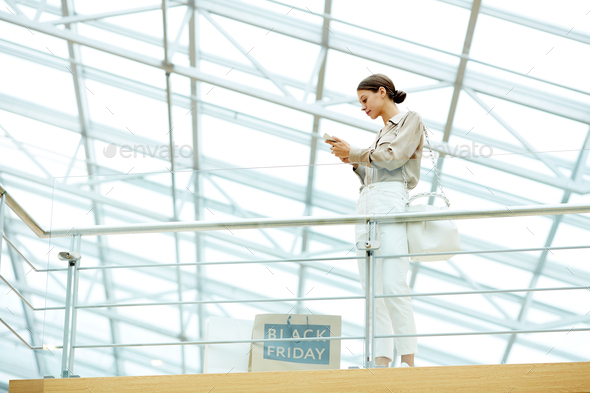 Businesswoman using phone in the mall - Stock Photo - Images