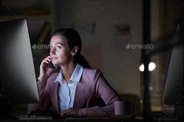 Businesswoman talking on the phone in dark office - Stock Photo - Images
