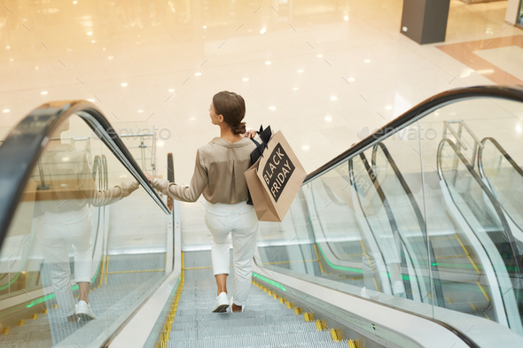 Woman standing on escalator - Stock Photo - Images