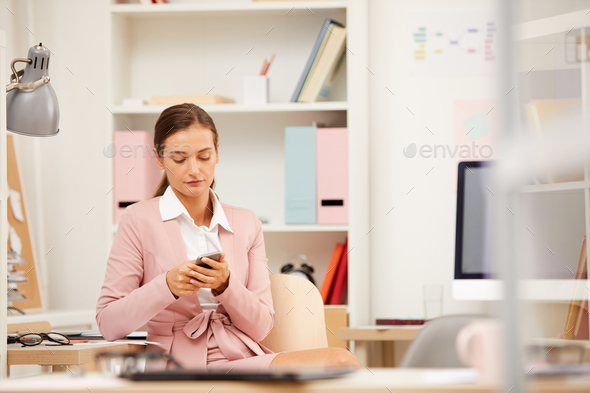 Businesswoman with phone at office - Stock Photo - Images